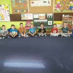 Na dywanie w półokręgu siedzi trzynastu chłopców.