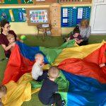 Na środku zdjęcia na ziemi położona jest okrągła kolorowa chusta na której siedzi 2 chłopców. Dookoła chusty siedzą dwie naczycielki trzymając na kolanach po jednym dziecku.