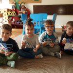 Czterech siedzących chłopców trzymających upominki