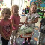 Cztery dziewczynki trzymające kosz z upominkami