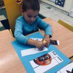 Chłopiec siedzący przy stoliku wykonujący pracę plastyczną