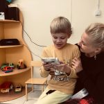 Chłopiec siedzący u pani na kolanach oglądający pudełko z kredkami
