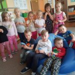 Grupa siedmiu stojących dziewczynek i czterech chłopców siedzących na siedzisku