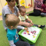 Dwoje chłopców wyciąga małe kolorowe piłki z miski wypełnionej miękkim puchem. Jeden chłopiec siedzi na zielonym dywanie, drugi na kolanach u Pani ubranej w szarą bluzkę.