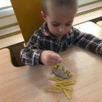 Chłopiec w koszuli z kratę siedzy przy stoliku. Przed sobą ma zrobionego jeża z masy solnej i makaronu rurki