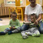 Dwoje dzieci siedzi na dywanie w tym jeden oparty jest o nauczycielkę w białej bluzce. Dzieci trzymają w rękach papierowe rurki od ręcznika papierowego,