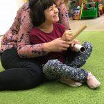Uśmiechnięta dzieeczynka siedzi na dywanie. Za nią siedzi Pani w różowej bluzce w białe i czarne kwiatki. Dziewczynka trzyma w rękach rurki papierowe.
