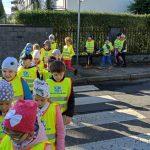 Grupa dzieci ubrana w żółte kamizelki przechodzi parami przez przejście dla pieszych.