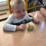 Chłopiec w białej bluzce siedzy przy stoliku. Przed sobą ma zrobionego jeża z masy solnej i makaronu rurki