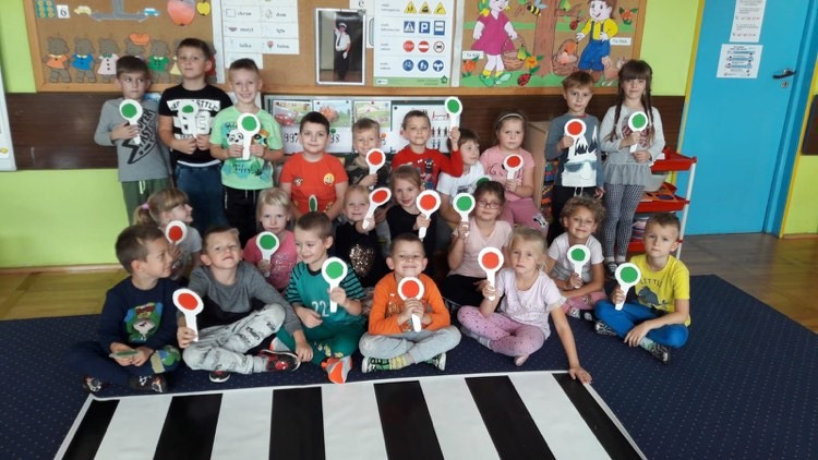 Grupa dzieci stoi lub siedzi uśmiechając się do aparatu. W rękach trzymają papierowe lizaki policujne z czerwonym lub zielonym światłem.