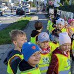 Pięcioro dzieci stoi zwrócone w stronę aparatu, za nimi jest droga na której jadą samochody i pali się zielone światło na sygnalizacji