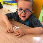 Uśmiechnięte dziecko z okularach trzyma z ręku kulkę z masy solnej.