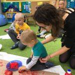 Dziecko z pomocą nauczycielki trzymającej jego rękę odbija na kawałku brązowej trektury stempel zrobiony w jabłka przekrojonego na pół i umaczanego z czerwonej farbie. za dzieckiem siedzi chłopiec w żółtej bluzce.