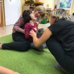 Uśmiechnięta dziewczynka siedzi na dywanie. Za nią siedzi Pani w różowej bluzce w białe i czarne kwiatki. Druga Pani ubrana w czarne ubrania pokazuje dziecku pluszowego, szarego jeżyka.