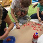 Dziecko z pomocą nauczycielki trzymającej jego rękę odbija na kawałku brązowej trektury stempel zrobiony w jabłka przekrojonego na pół i umaczanego z czerwonej farbie