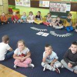 Dzieci siedzą w kole. Na środku leża obrazki i zakładki do książki