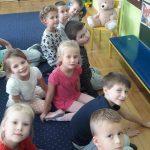 10 dzieci siedzi na dywanie i uśmiecha się do aparatu. Zvtyłu widać misia pluszowego posadzonego na krześle