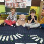 Dziewczynka i chłopiec siedzą na dywanie, po środku siedzi pluszowy miś. Przed nimi leżą zakładki do książek.