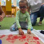 chłopiec w okularach odbija stempel na kawałku brązowej trektury zrobiony w jabłka przekrojonego na pół i umaczanego z czerwonej farbie