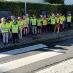 duża grupa dzieci ustawiona jest w pary. każde dziecko ma na sobie żółtą kamizelkę. Przed dziećmi widać pasy- przejście dla pieszych.