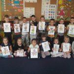 Duża grupa dzieci trzyma pokolorowane rysunki