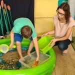 Chłopiec stoi w dmuchanym basenie, trzyma w rękach małą siatkę . Zamacza ją w pudełku wypełnionym wodą. W basenie umieszczony jest piasek i kamienie. Obok chłopca kuca nauczyclka.