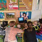 Grupa dzieci i 2 panie siedzą na krzesłach tyłem do zdjęcia. Przed nimi siedzi Pani z laptopem.