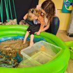 Dziewczynka siedzi na kolanach u PanJej stopy dotykają piasku umieszczonego w małym, dmuchanym basenie.