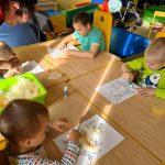 Czworo chłopców wiedzi na krzesłach przy stolikach. Trzymają w rękach klej lub piórka. Przed nimi leży kartka z konturem małej kaczuszki.