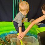 Chłopiec stoi w dmuchanym basenie, trzyma w rękach małą siatkę . Zamacza ją w pudełku wypełnionym wodą. W basenie umieszczony jest piasek i kamienie.