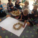 Chłopiec sieczący na dywanie, układający koło z ziemniaków na białym brystolu. Za nim siedzące w półkolu dzieci, przed którymi stoi kosz z ziemniakami.