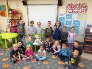 Grupa dzieci na dywanie, pomiędzy którymi siedzi pluszowy miś