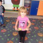 Dziewczynka stojąca na dywanie, trzymająca drewnianą łyżkę, na której znajduje się ziemniak. Za nią stoi chłopiec.