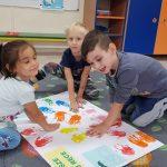 Troje dzieci odbijających pomalowane farbami dłonie na brystolu