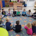 Grupa dzieci siedzących w kole na dywanie