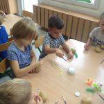 Dzieci siedzące przy stolikach, ozdabiające ziemniaki.