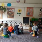 Grupa dzieci bawiących się na dywanie klockami oraz autem