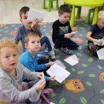 Pięcioro dz0ieci siedzących na dywanie i trzymających kartki papieru