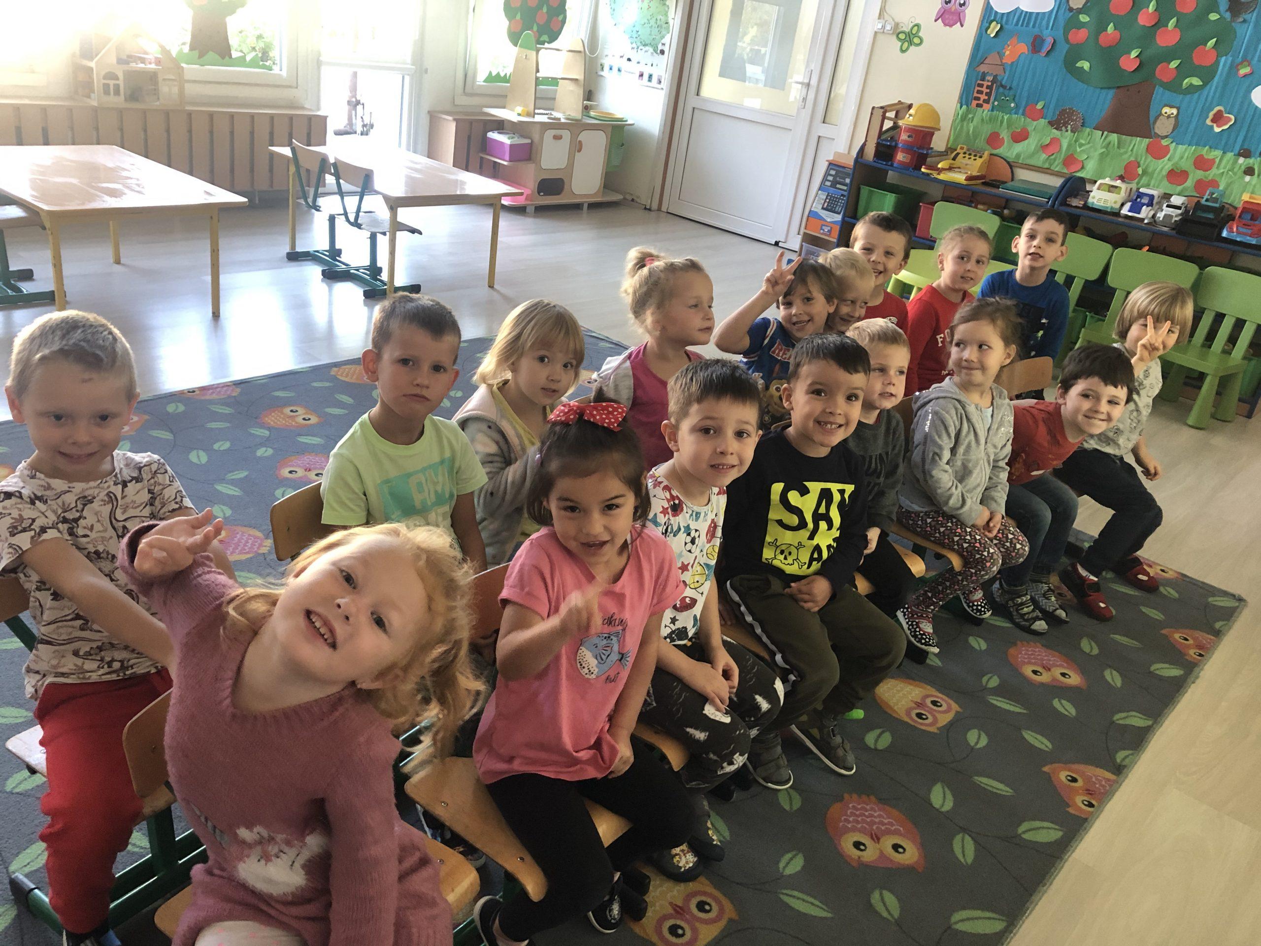 Grupa dzieci siedzaca na krzesłach w dwóch rzędach