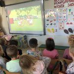 Dziewięcioro dzieci siedzących na krzesłach i oglądających bajkę na tablicy interaktywnej