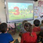 Czworo dzieci siedzących na krzesłach i oglądających bajkę na tablicy interaktywnej