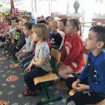 Grupa dzieci siedzących na krzesłach w dwóch rzędach