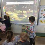 Dwoje dzieci stojacych przy tablicy interaktywnej i rozwiązujących zadanie. Przed nimi dwoje dzieci