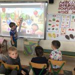 Chłopiec stojący przy tablicy interaktywnej rozwiązujący zadanie. Przed tablicą czworo dzieci siedzących na krzesłach.