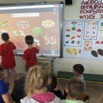 Dwoje dzieci stojących przed tablicą interaktywną i rozwiązujących zagadki
