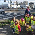 Grupa dzieci idących chodnikiem wraz z panią