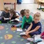 Ośmioro dzieci siedzących na dywanie i trzymających kartki papieru