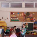 Pięcioro dzieci bawiących się na dywanie. Obok nich chłopiec siedzący na krześle.