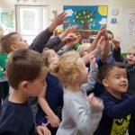 Grupa dzieci trzymających ręce do góry