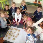 Grupa dzieci siedzących na dywanie i układających na białym brystolu wzór z ziemniaków.